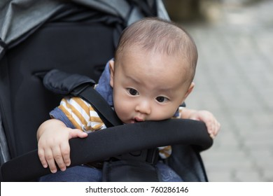 Outdoor zooming closeup portrait of a young lovely little Asian baby boy dresses in colorful suit sitting in a black perambulator while looking curiously on something in front of him . Nobody else