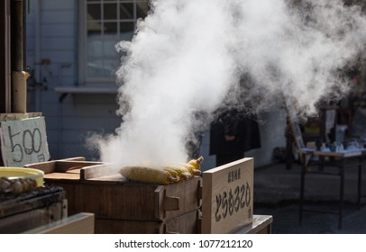 Outdoor zooming closeup view of grilled corns on vintage Japanese wooden broiler in front of an entrance to village Oshino Hakkai nearby Mount Fuji , Japan in March 17 2018.
