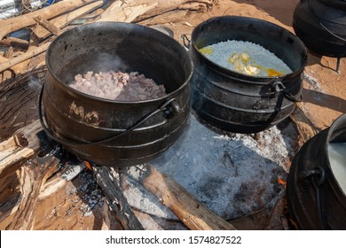 Outdoors African cooking in the kitchen with three legged pots for celebrations and weddings