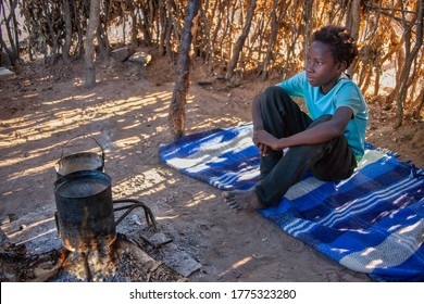outdoors african kitchen, sited girl on a blanket waiting for the water to boil on the two pots
