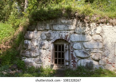 Outdoors built structure of the old ancient underground stone house under the green grass.