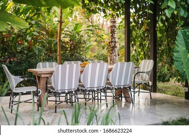 Outdoors cafe with empty dining room table and wicker chairs against natural background at sunny summer day