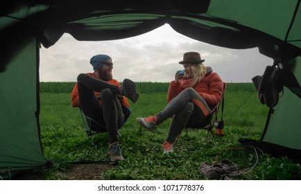 outdoors couple (man and woman) sitting in front of a tent on camping chairs