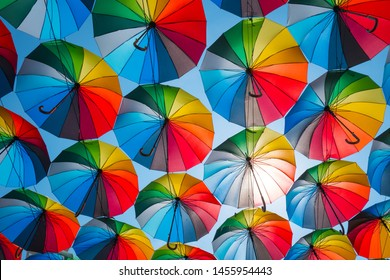 outdoors decoration with many colorful umbrellas against blue sky and sun