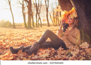 Outdoors fashion image of stunning young woman sitting on the grass in magical autumn park. Holding in arms bunch of grapes. Wearing stylish pullover and a wreath of autumn leaves. Autumn colours.