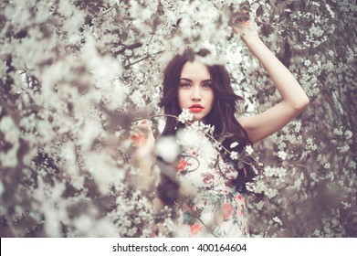Outdoors fashion photo of beautiful young lady in the garden of cherry blossoms
