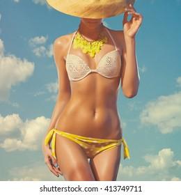 На открытом воздухе мода фото молодой леди с идеальным телом в купальнике против неба