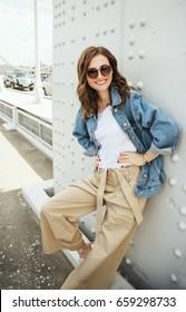 Outdoors fashion portrait of cheerful trendy woman posing on the street. Smiling and walking on the city. Going shopping. Wearing stylish wide jean jacket, beige slacks and sunglasses.