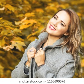 Outdoors fashion portrait of happy stunning young woman walking in the magical autumn park. Wearing stylish grey coat, silver rings. Smiling, enjoying life. Bright make up, long curly hair. Red leaves