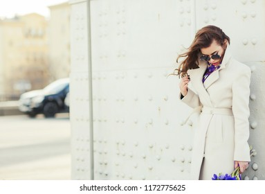 Outdoors fashion portrait of stunning trendy woman posing on the street. Smiling and walking on the city. Going shopping. Wearing stylish white fitted coat, round rim sunglasses. Waiting for. Close up