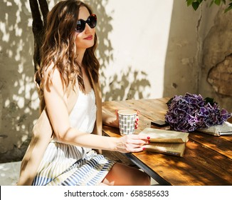 Outdoors fashion portrait of stunning woman sitting in cafe. Drinking coffee and reading old book. Wearing stylish long beige waistcoat, striped skirt and vintage sunglasses. Close up. Get inspired
