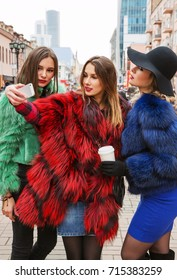 Outdoors fashion portrait of three young pretty smiling girls friends walking at the city. Making selfie. Shopping. Posing at the street. Wearing bright colored fur coats. Make up. Positive emotions