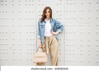 Outdoors fashion portrait of trendy pretty girl posing on the white wall background. Smiling and walking on the city. Going shopping. Wearing stylish wide jean jacket and beige slacks. Pensive mood