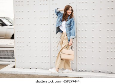 Outdoors fashion portrait of trendy pretty girl posing on the white wall background. Smiling and walking on the city. Going shopping. Wearing stylish wide jean jacket, beige slacks. Positive emotione