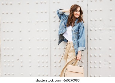 Outdoors fashion portrait of trendy pretty girl posing on the white wall background. Smiling and walking on the city. Going shopping. Wearing stylish wide jean jacket, beige slacks. Positive emotion
