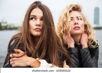 Outdoors fashion portrait of two beautiful girls friends walking on the city. City background. Wearing stylish outerwear. Young and sensual. Wind in the hair. Bright make up and long hair. Close up