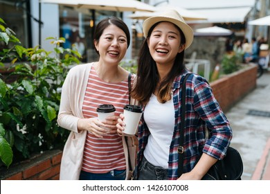 Outdoors fashion portrait of two cheerful asian girls friends drinking coffee holding paper cup walking in city. young women laughing looking aside at funny thing happened in small village market.