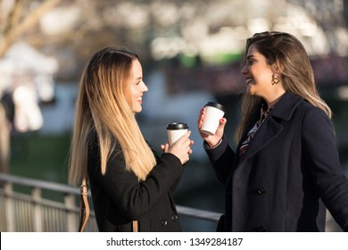 Outdoors fashion portrait of two young beautiful women friends drinking coffee. Smiling and going shopping. Kissing a cup of coffee. Bright make up