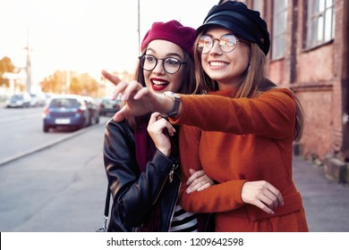 Outdoors fashion portrait young pretty best girls friends in friendly hug. Walking at the city. Posing at the street. Wearing stylish outerwear and hats. Bright make up. Positive emotions