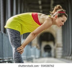 Outdoors fitness in Paris. young active woman catching breath after exercise on Pont de Bir-Hakeim bridge in Paris