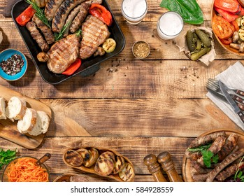 Outdoors Food Concept. Appetizing barbecued steak, sausages and grilled vegetables on a wooden picnic table with copy space, top view