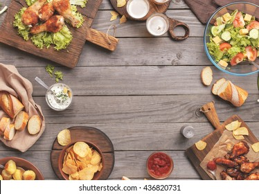 Outdoors Food Concept. On the wooden table different food with copy space, grilled chicken legs, buffalo wings, bread, salad, potatoes, potato chips and beer