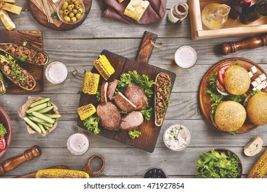 Outdoors Food Concept. On the wooden table different food steak, burgers, zucchini with meat bread, salad, bread, snacks and beer, top view