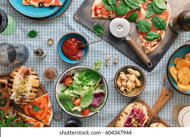 Outdoors food concept. Pizza, hot dogs, wine, beer and a snack for beer on the table, top view