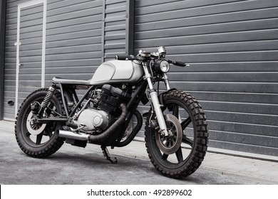 Outdoors grey rebuilt motorcycle motorbike cafe racer in front of rolled gates of garage