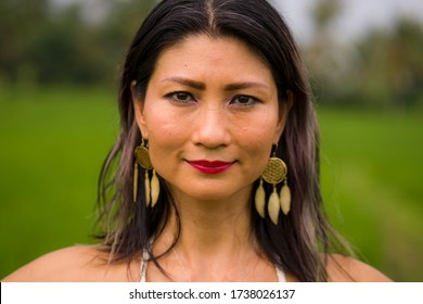 outdoors holidays portrait of attractive and happy middle aged Asian Korean woman in white dress enjoying freedom and nature at green field landscape carefree and cheerful