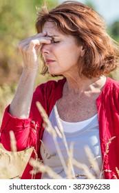 outdoors illness - beautiful mature woman having headache for rhinitis,allergies or hay fever reaction,summer daylight