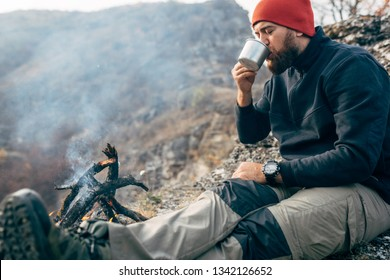 Outdoors image of young explorer man drinking hot beverage in mountains, sitting near to bonfire, relaxing after trekking. Traveler man in red hat holding a mug of tea after hiking. Travel, people