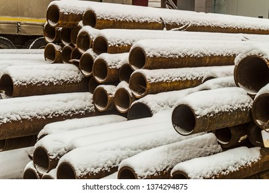 Outdoors industrial warehouse of finished steel pipes and metal products. Storage site at winter time.