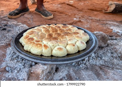 Outdoors kitchen in an African village frying bread called dipapata  on the lid of a large cast iron pot