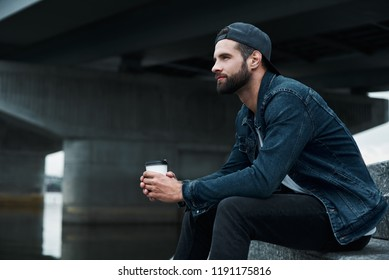Outdoors leisure. Young stylish man sitting on stairs on city street holding cup drinking hot coffee looking forward enjoying view smiling confident