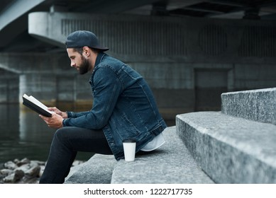 Outdoors leisure. Young stylish man sitting on stairs on city street with cup of hot coffee reading book joyful side view