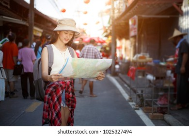 Outdoors lifestyle of beautiful young woman.  traveler young woman  standing  looking map smiling on holiday festival outdoor market famous with backpack , tourism shopping  Festive mood, Traveler
