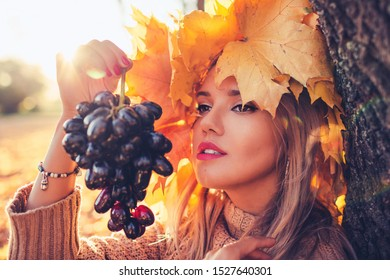 Outdoors lifestyle fashion close up image of stunning young woman in autumn park. Holding in arm bunch of grapes. Wearing stylish pullover and a wreath of autumn leaves. Autumn colors. Dreaming.