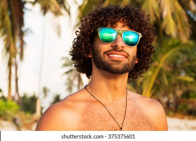 Outdoors lifestyle fashion close up portrait of pretty handsome guy, smiling and having fun. Wearing stylish sunglasses. In sunglasses reflected sea. Curly long dark hair and stylish beard