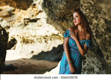 Outdoors lifestyle fashion image of stunning young woman posing near cliff on the tropical beach. Wearing stylish long summer blue dress. Bright make up and long curly hair. Summer holiday concept