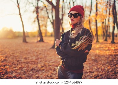 Outdoors lifestyle fashion portrait of beautiful trendy girl walking on the autumn park. Wearing stylish bomber jacket, hat, sunglasses and leather leggins. Enjoying autumn nature.   Autumn colors