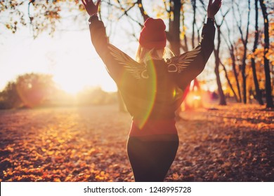 Outdoors lifestyle fashion portrait of beautiful trendy girl walking on the autumn park. From the back. Wearing stylish bomber jacket, hat and leather leggins. Enjoying autumn nature. Autumn colors