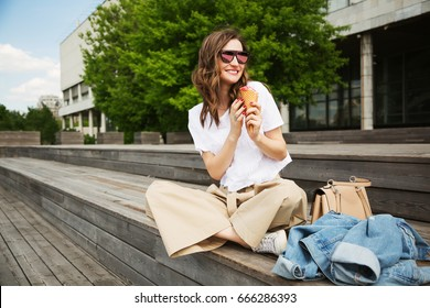 Outdoors lifestyle fashion portrait of cheerful trendy woman sitting on the wood bench. Eating ice-cream, smiling and walking on the city. Going shopping. Wearing stylish beige slacks and sunglasses