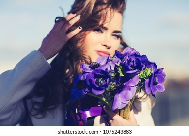 Outdoors lifestyle fashion portrait of happy gorgeous brunette girl. Smiling and holding bouquet of flowers. Wearing stylish purple neck scarf. Happiness concept. Close up. Wind in the hair. Sunny day
