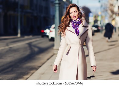 Outdoors lifestyle fashion portrait of happy gorgeous brunette girl. Beautiful smile. Walking to the city street. Wearing stylish white fitted coat, purple neckscarf. Romantic mood. Beauty face