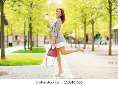 Outdoors lifestyle fashion portrait of happy pretty ginger hair girl. Smiling, drinking coffee, walking on the city street. Going shopping.  Wearing stylish checkered jacket, sunglasses, dress