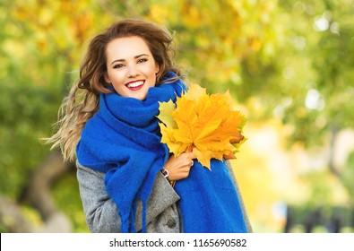 Outdoors lifestyle fashion portrait of happy pretty girl walking on the autumn park. Holding maple leaves. Wearing stylish blue scarf, grey coat. Smiling, enjoying autumn nature. Jogging, having fun