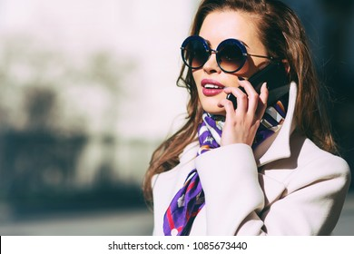 Outdoors lifestyle fashion portrait of pretty young woman talking on the phone. Smiling, walking on the city street. Going shopping. Wearing stylish white fitted coat, purple neckscarf, round sunglass