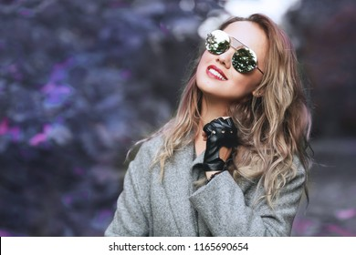 Outdoors lifestyle fashion portrait of pretty young woman walking on the autumn park.  Wearing stylish grey coat, mirorred sunglasses and glovelettes. Enjoying autumn nature. Autumn colors. Close up