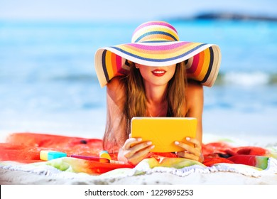 Outdoors lifestyle fashion portrait of pretty girl watching movie on tablet on the beach. Wearing  wide brimmed hat with stripes. Sunbating with uv protection. Concept of tropical beach vacation